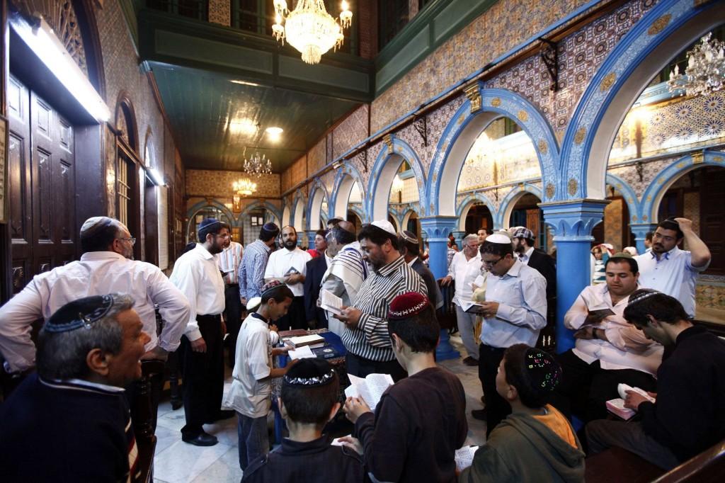 Jewish men pray inside the blue-tiled El Ghriba synagogue on the Tunisian island of Djerba following a wedding ceremony