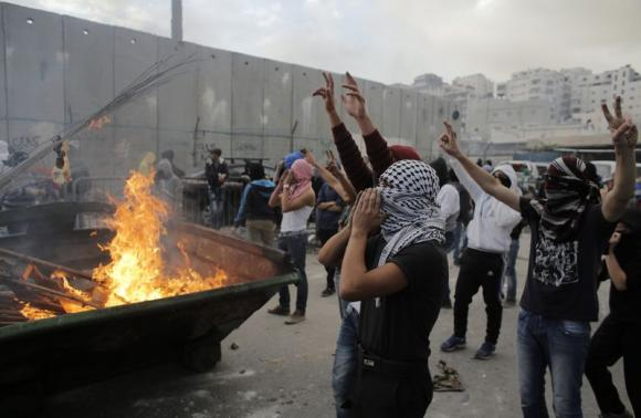 Palestinian stone-throwers gesture in front of garbage set ablaze during clashes with Israeli police on outskirts of Jerusalem