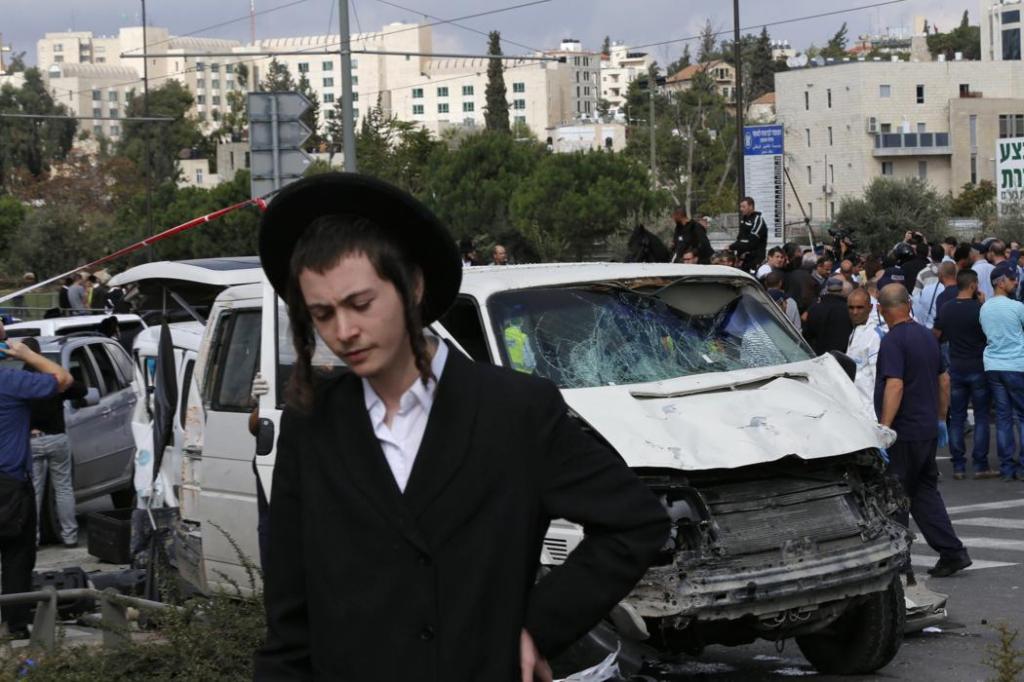 Ultraortodox fiú a merényletetben részt vevő furgon előtt (fotó Ammar Awad, Reuters, forrás news.yahoo.com)