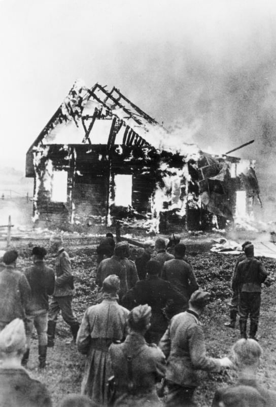 """Scherl: Von Litauern in Brand gesteckte Synagoge.  Die Erbitterung gegen die jüdischen Verbrecher ist in den baltischen Ländern besonders groß, denn gerade die Juden waren es, die der GPU zahllose unschuldige Opfer in die Hände spielten und der Ermordung oder Verbrennung auslieferten. PK - Zoll - Scherl.  9.7.41 [Herausgabedatum] AV 64149 """"Fr"""" OKW ADN-Bildarchiv: II. Weltkrieg 1939-45 In einem litauischen Ort beobachten Soldaten der faschistischen deutschen Wehrmacht und Einheimische das Niederbrennen einer angezündeten Synagoge. Aufnahme: Zoll/Juni 1941"""