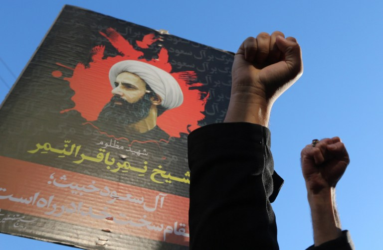 Iranian protesters raise their fists in front of a portrait of prominent Shiite Muslim cleric Nimr al-Nimr during a demonstration against his execution by Saudi authorities, on January 3, 2016, outside the Saudi embassy in Tehran. Iran and Iraq's top Shiite leaders condemned Saudi Arabia's execution of Nimr, warning ahead of protests that the killing was an injustice that could have serious consequences. AFP PHOTO / ATTA KENARE / AFP / ATTA KENARE