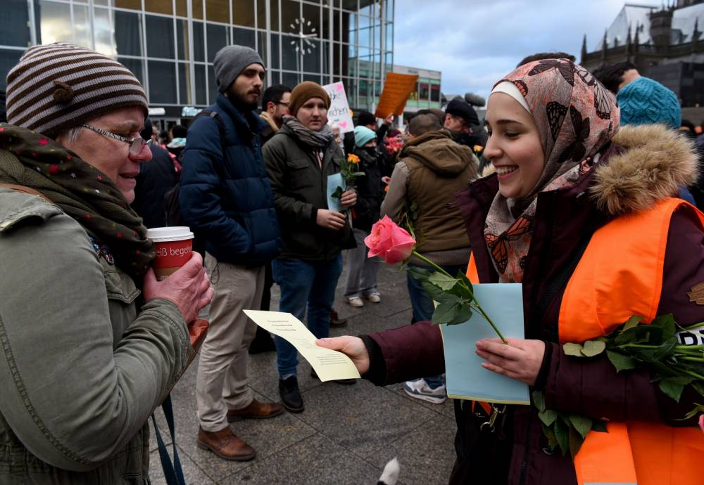 """Refugees from Syria present flowers to passers-by as they demonstrate against violence near the Cologne main train station in Cologne, western Germany on January 16, 2016, where hundreds of women were groped and robbed in a throng of mostly Arab and North African men during New Year's festivities. German authorities said that nearly all the suspects in a rash of New Year's Eve violence against women in Cologne were """"of foreign origin"""", as foreigners came under attack amid surging tensions. / AFP / PATRIK STOLLARZPATRIK STOLLARZ/AFP/Getty Images"""