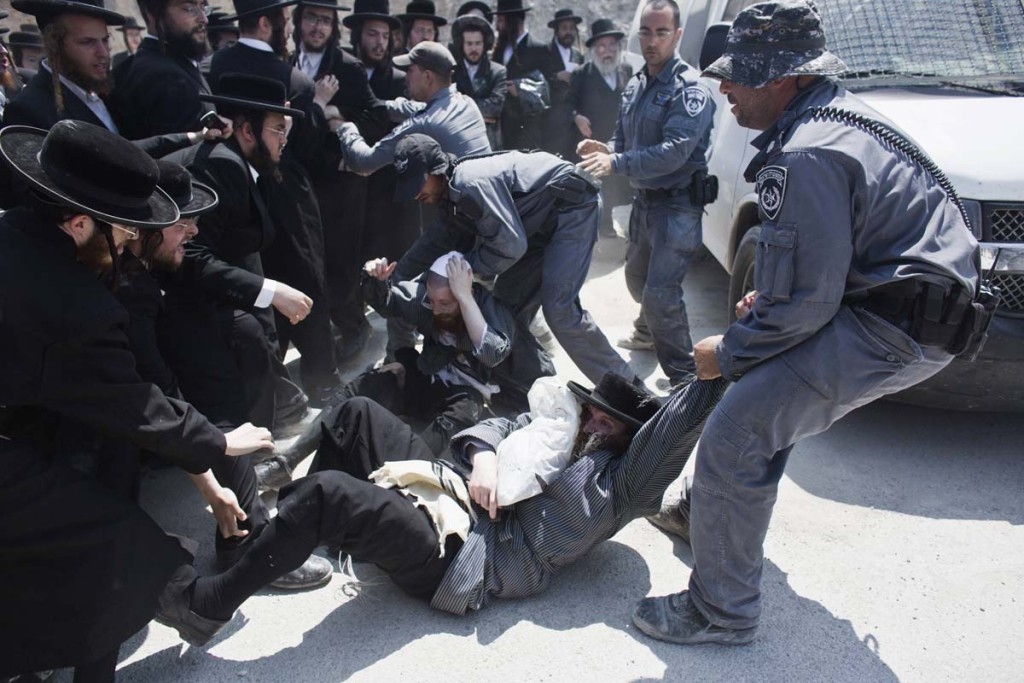 Israeli policemen drag ultra-Orthodox protesters during clashes in the town of Beit Shemesh, near Jerusalem August 12, 2013. An Israeli police spokesperson said some 21 ultra-Orthodox protesters were detained on Monday in the town during clashes with police after a group of them broke into a construction site to prevent work from taking place at the site they believe contains ancient graves. REUTERS/Nir Elias (ISRAEL - Tags: POLITICS RELIGION CIVIL UNREST) ORG XMIT: JER10