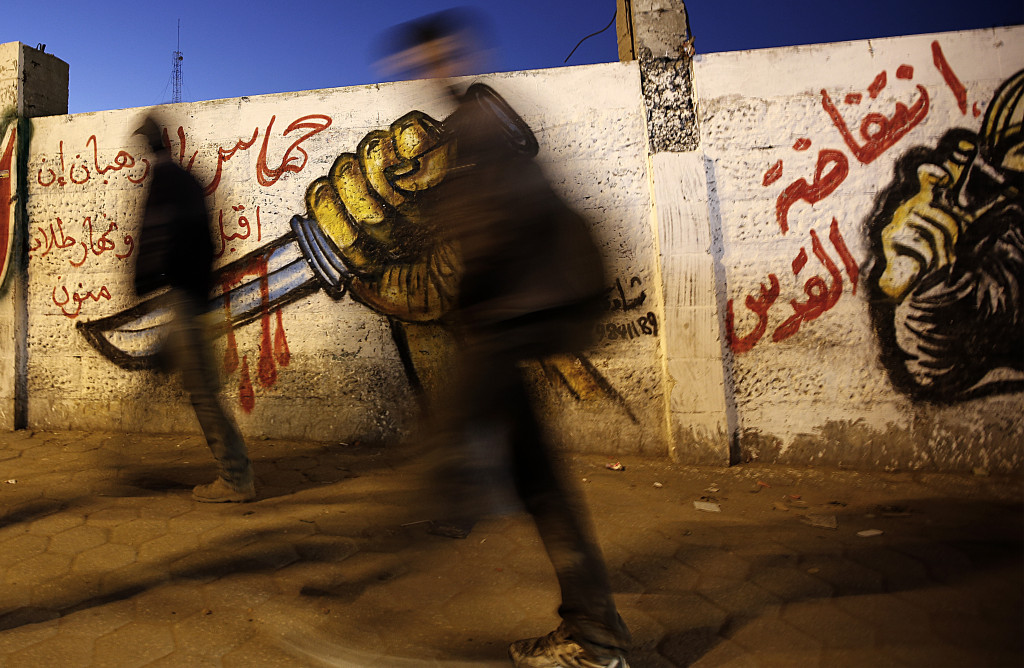 epa05117131 Palestinians walk in front of a graffiti depicting a hand holding a knife, in support of the third Palestinian 'intifada' or uprising, in the streets of Gaza City, 21 January 2016. EPA/MOHAMMED SABER