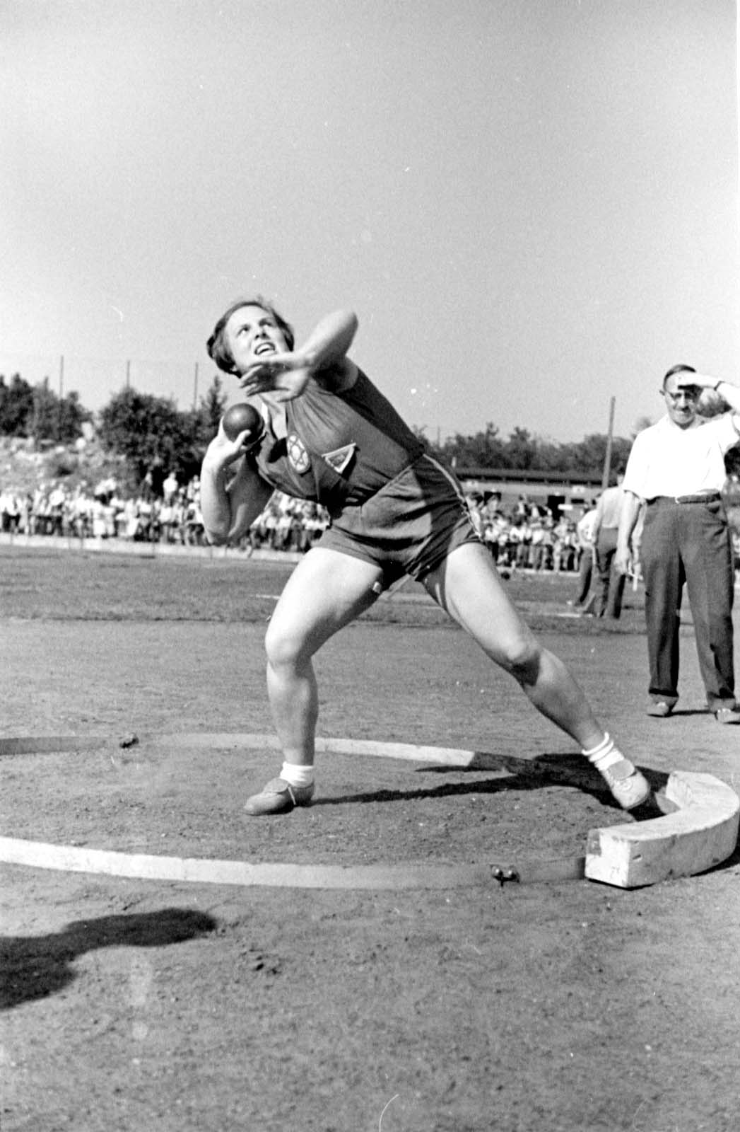 """Berlin, Germany, 1937, Selma Schulmann in the shot-put event at the """"Bar-Kochba"""" international sports games with the participation of """"Hakoach Vienna"""". The games took place at the Grunewald field and included soccer, handball and hockey."""