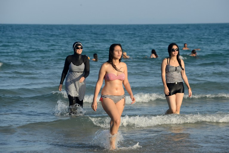 """(FILES) This file photo taken on August 16, 2016 shows Tunisian women, one (L) wearing a """"burkini"""", a full-body swimsuit designed for Muslim women, walking in the water at Ghar El Melh beach near Bizerte, north-east of the capital Tunis.  The debate launched this summer in France over the Burkini is not causing such a stir in North Africa where the Islamic swimsuit is uncontroversial as the dress-code on the beaches has become increasingly prudish.  / AFP PHOTO / FETHI BELAID / TO GO WITH AFP STORY BY AMAL BELLALOUFI WITH AFP CORRESPONDENTS IN RABAT AND TUNIS"""