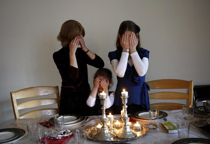 Female members of the Nogradi family light candles at the Sabbath in their home in Budapest November 30, 2012. It is only relatively recently that Hungary's Jews have celebrated their identity as openly as they did when Europe's largest synagogue was built in Budapest in the 1850s. Now they are determined not to allow a political climate in which they have to defend that identity or even suppress it. Although anti-Semitism has not yet led to serious physical confrontations, hate crimes have included desecration of Jewish cemeteries and a verbal attack in Budapest on 90-year-old former Chief Rabbi Joseph Schweitzer. Picture taken November 30, 2012. To match HUNGARY-JEWS/ REUTERS/Bernadett Szabo (HUNGARY - Tags: RELIGION POLITICS SOCIETY) - RTR3BMUH