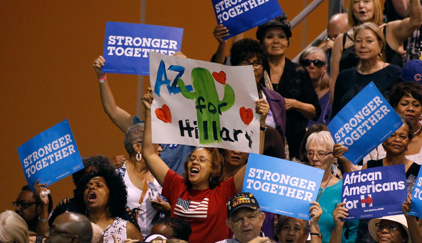 PHOENIX, AZ - OCTOBER 20:  Supporters for presidential nominee Hillary Clinton hold up signs and cheer as first lady Michelle Obama speaks at an Arizona Democratic Party Early Vote rally on October 20, 2016 in Phoenix, Arizona.  (Photo by Ralph Freso/Getty Images)